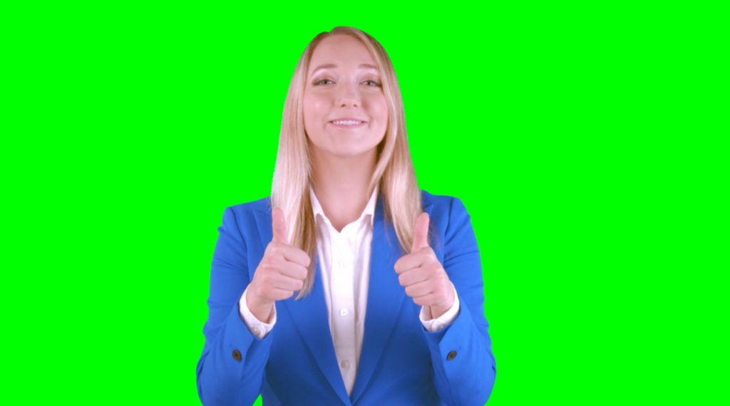 Young lady making the thumbs up gesture with a green screen behnd her.
